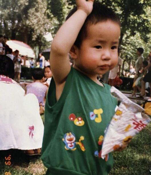 王一博童年照 身穿草绿色背心短裤套装